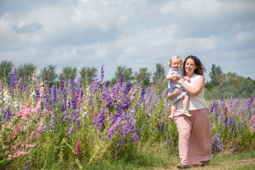 confetti fields photoshoots mother and toddler walking through delphinums